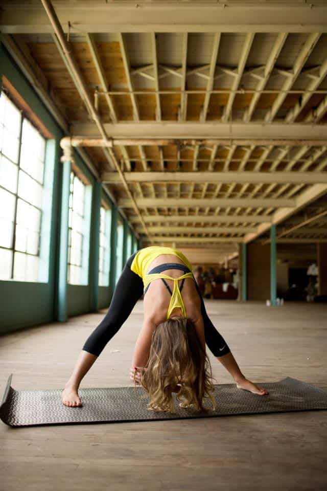 Kalee doing wide leg forward fold yoga move