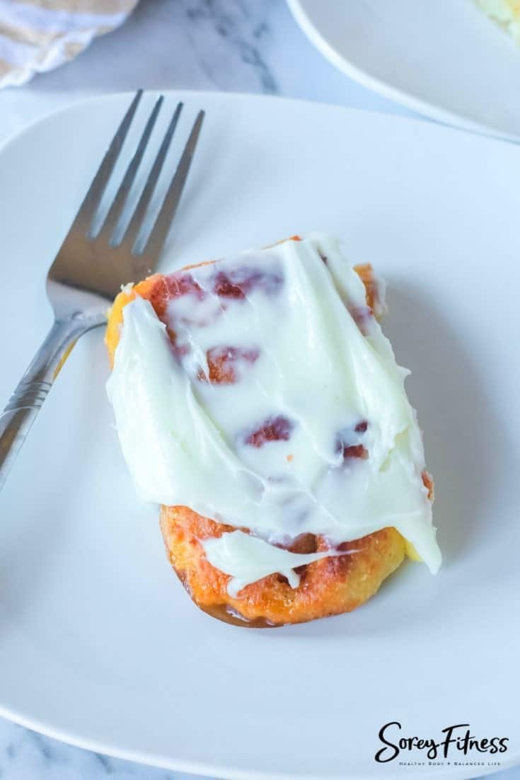 low carb cinnamon roll with cream cheese frosting on a plate with a fork