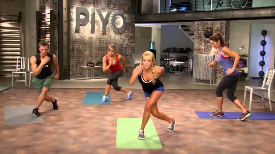 Chalene and cast in a bowlers lunge during a piyo workout