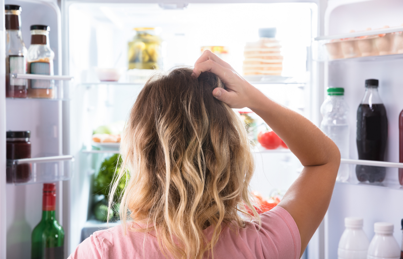 woman confused at the fridge