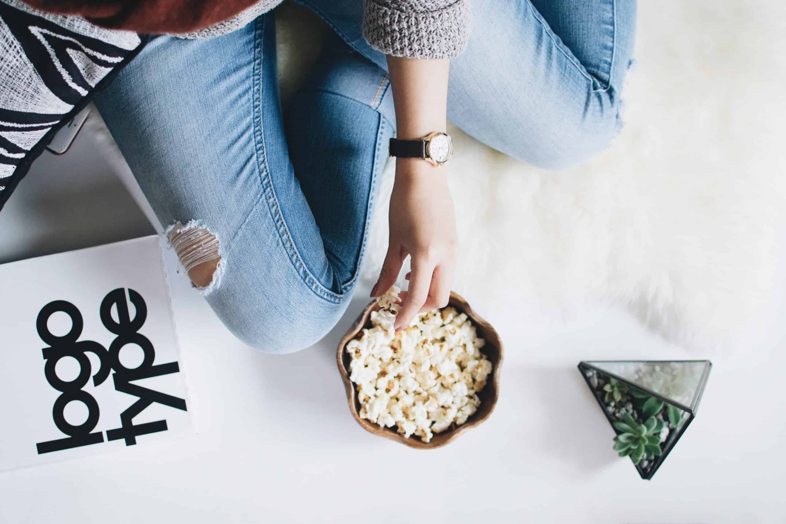woman sitting with a bowl of popcorn