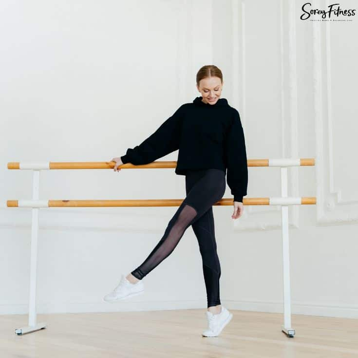 woman holding onto a ballet barre with leg lifted