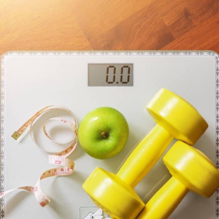 scale with an apple, measuring tape, and weights on it