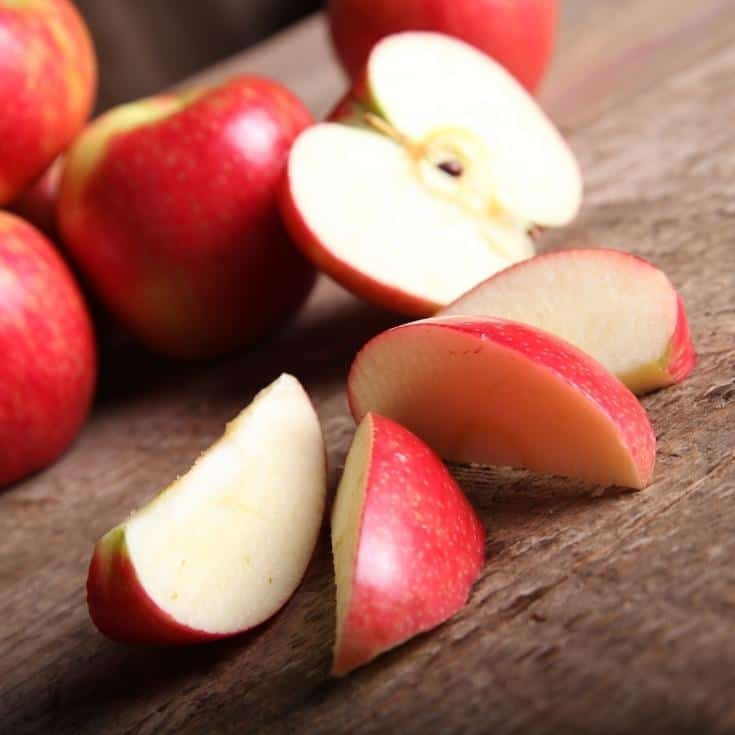 cut up apples on a wooden board